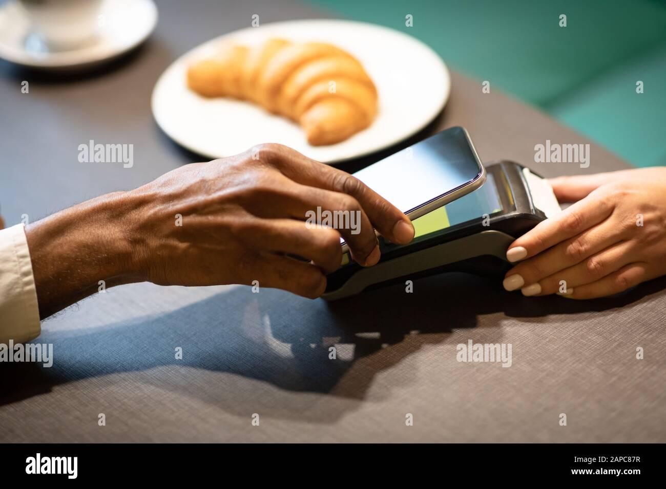 Afro-Geschäftsmann zahlt mit Handy an der Bar Stockfoto