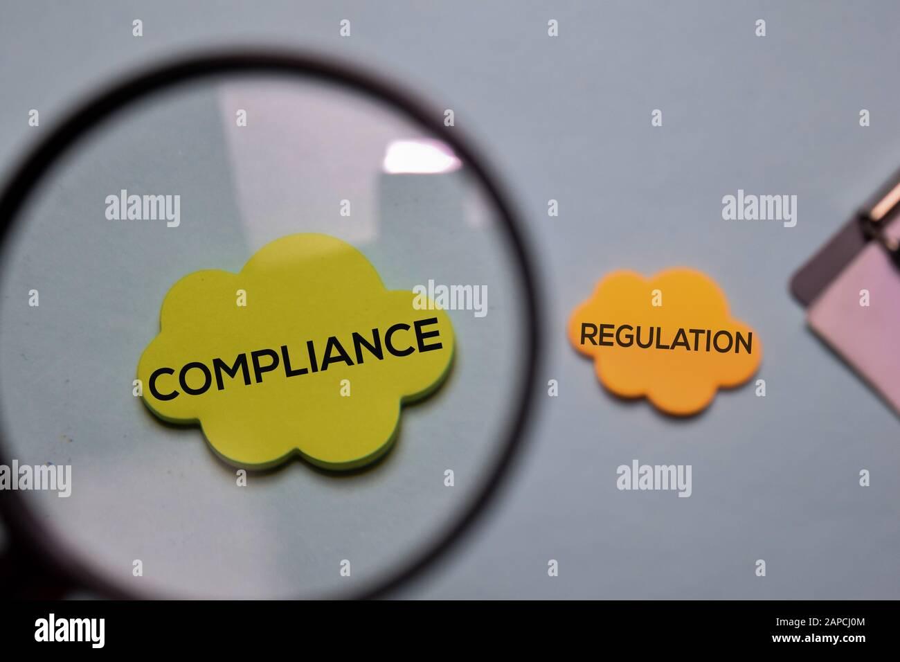Compliance und Regulierung schreiben Sie auf einen Haftnotiz, der auf dem Schreibtisch isoliert ist. Stockfoto