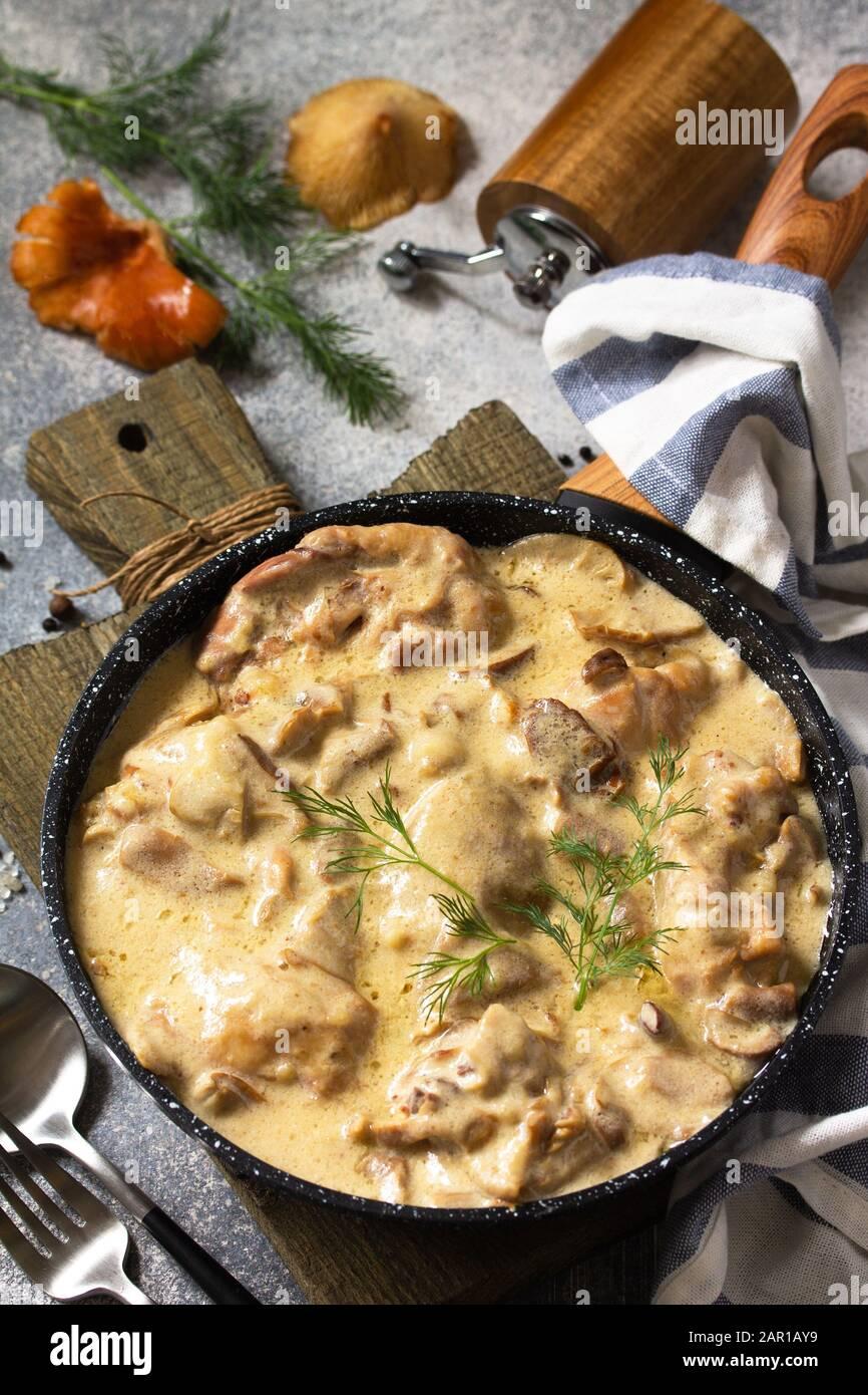 Fricasse - Französische Küche. Huhn in einer cremigen Soße mit Pilzen in einer Pfanne auf hellem Steingrund gehütet. Stockfoto