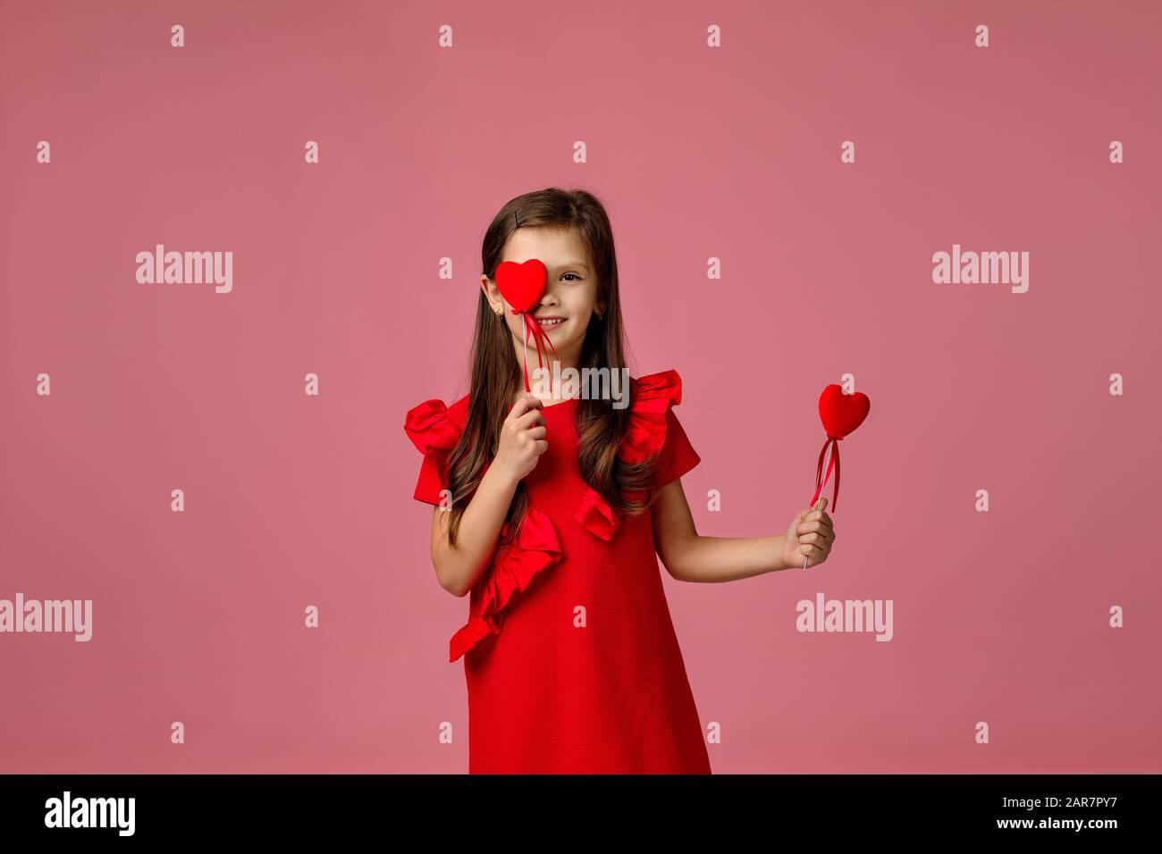 Valentinstag. Lächelndes Kindermädchen mit zwei roten Herzen isoliert auf pinkfarbenem Hintergrund. Stockfoto