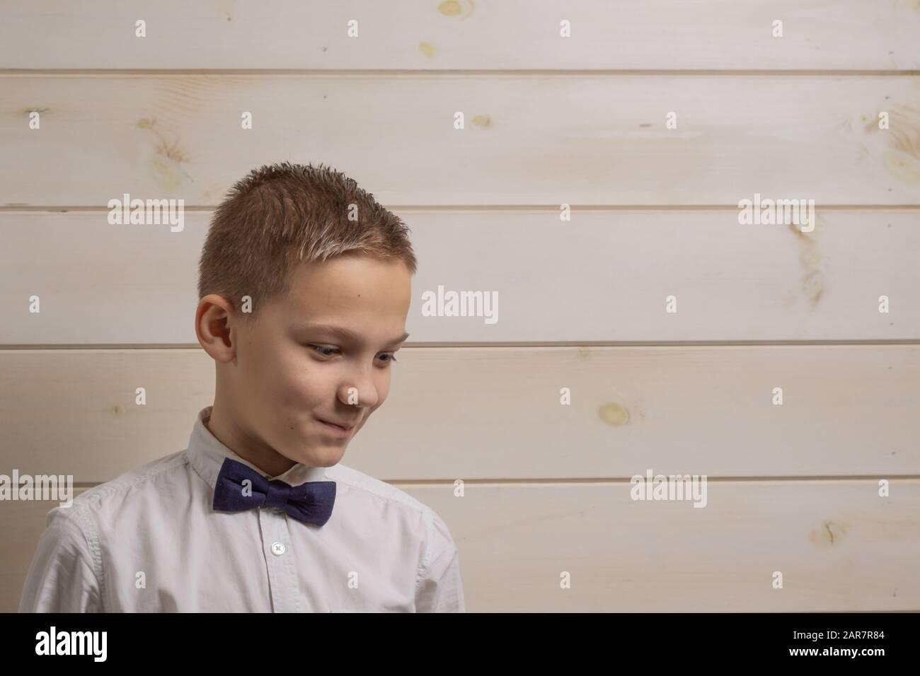 Ein zehnjähriger fadenhaariger Junge in einem weißen Hemd mit der selbstbinderigen Bow Tie lächelt vor dem Hintergrund einer Holzwand Stockfoto