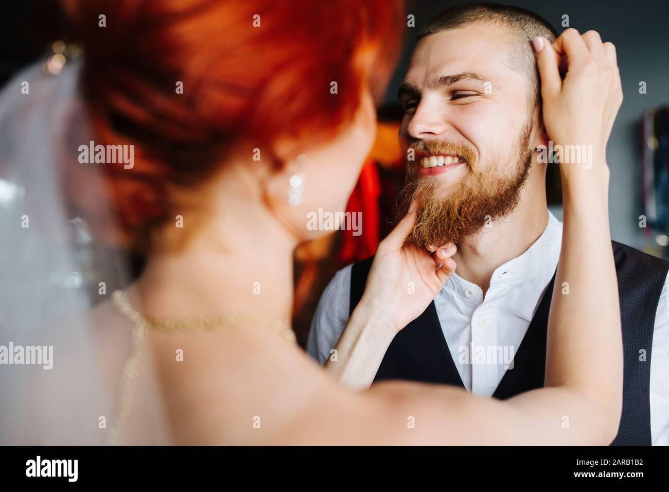 Die Brautpflege ihres zukünftigen Ehemannes in einem hellen Raum vor der Trauung Stockfoto