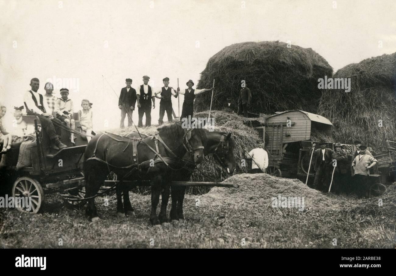 Deutschland Ernte - Landwirte, ihre Familien und ihre Kinder schneiden den Mais und betreiben eine winternde Maschine. Datum: Ca. 1906 Stockfoto