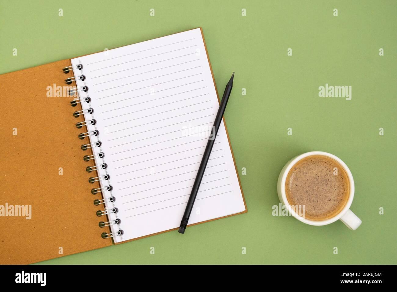 Öffnen Sie das Notebook mit leerer Seite und Kaffeetasse. Tischplatte, Arbeitsbereich auf grünem Hintergrund. Minimalistischer flacher Lay. Stockfoto
