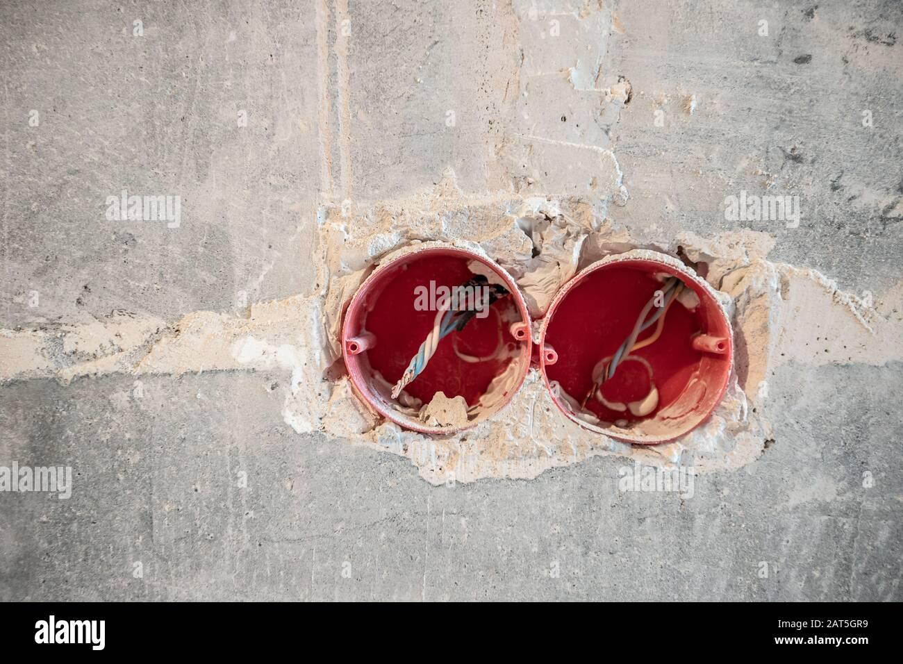 Zerlegte Steckdose in der Detonationswand mit blanken Drähten und Kennzeichen während der Reparatur in der Wohnung Stockfoto