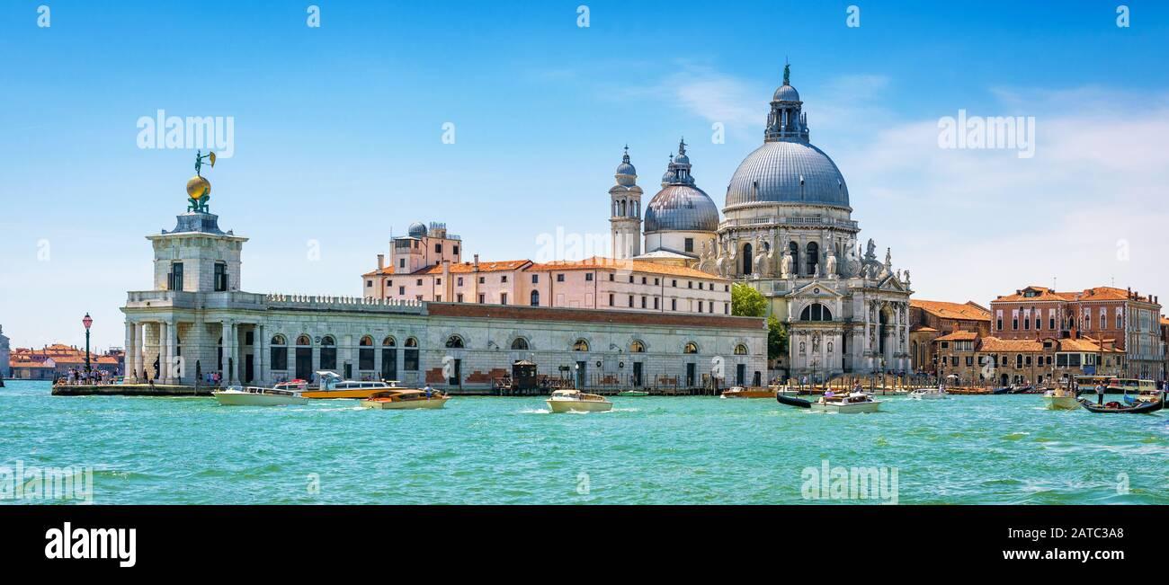 Panoramablick auf den Canal Grande mit Wassertaxis und die Kirche Santa Maria della Salute in Venedig, Italien. Motorboote sind der Haupttransport in Venedig. Stockfoto