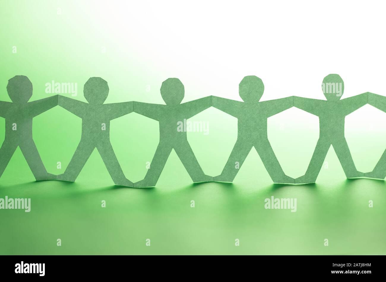 Team von Mitarbeitern der Papierkette. Menschenkette mit Licht und Schatten auf grünem Backgorund. Stockfoto