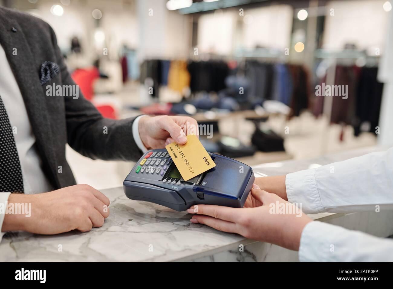 Nahaufnahme eines nicht erkennbaren Geschäftsmannes im Anzug, der an der Theke steht und mit kontaktloser Karte im Geschäft bezahlt Stockfoto