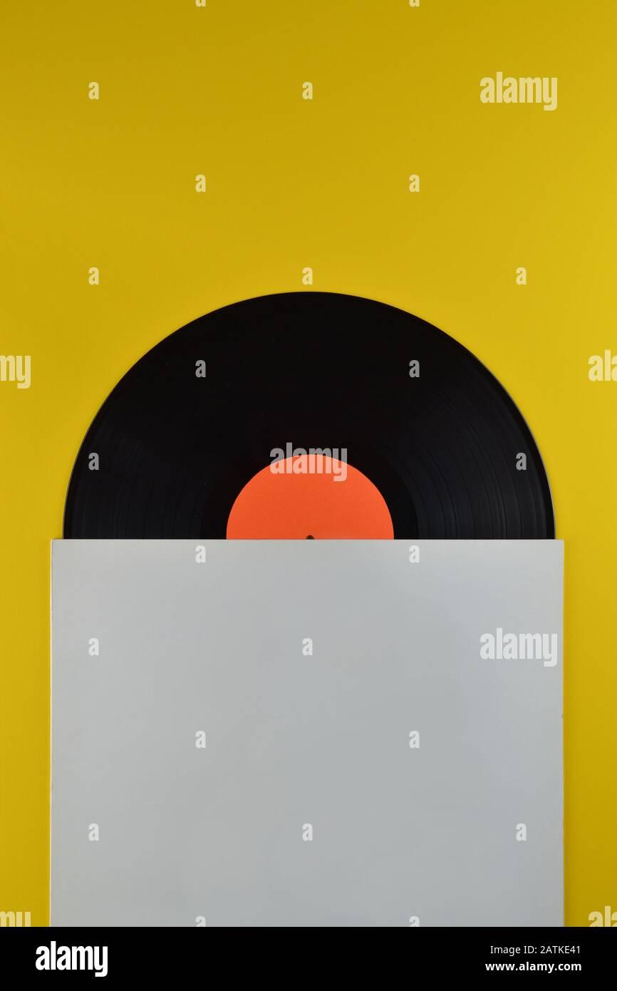 Alte schwarze Schallplatte mit leerem orangefarbenem Label, halb aus der weißen leeren Abdeckung auf gelbem Hintergrund Stockfoto