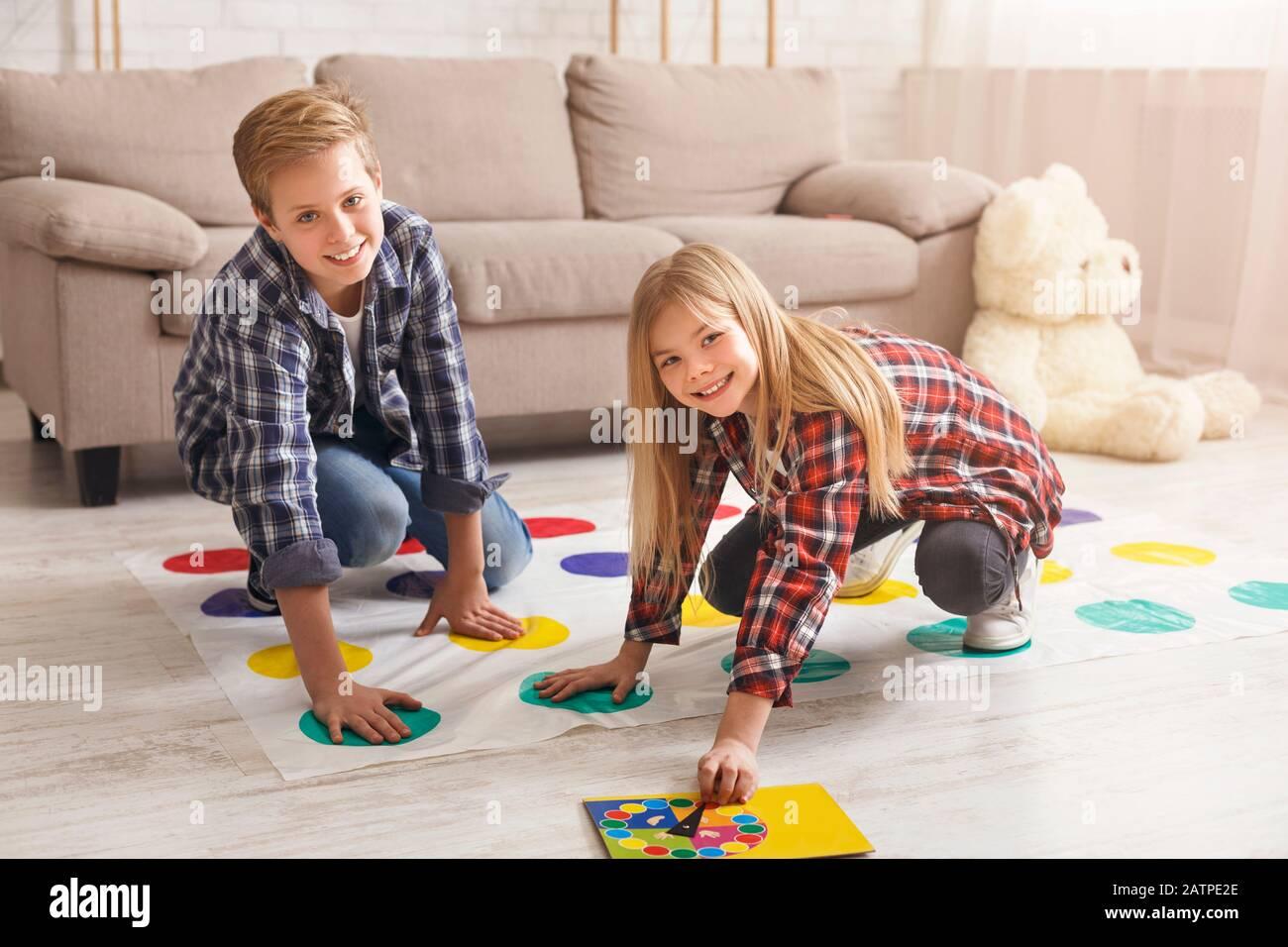 Fröhliche Geschwister, die Twister-Spiel auf dem Boden spielen und Spaß in der Halle haben Stockfoto