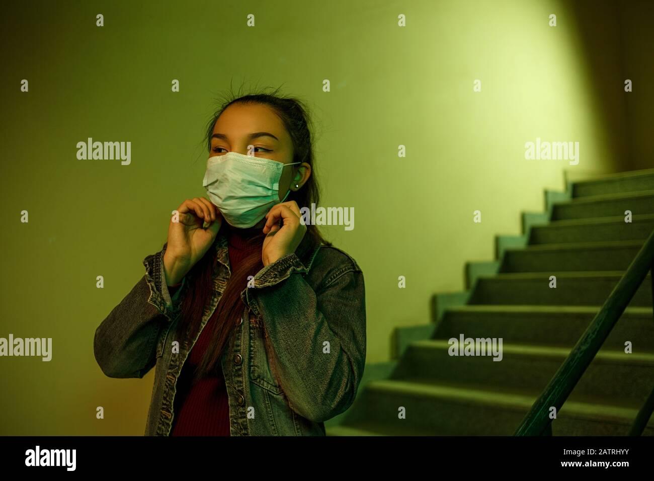 Porträt einer asiatischen jungen Frau. Treppenhaus des Krankenhauses. Das Mädchen trägt eine Maske, um sich nicht mit dem Virus infizieren zu lassen Stockfoto