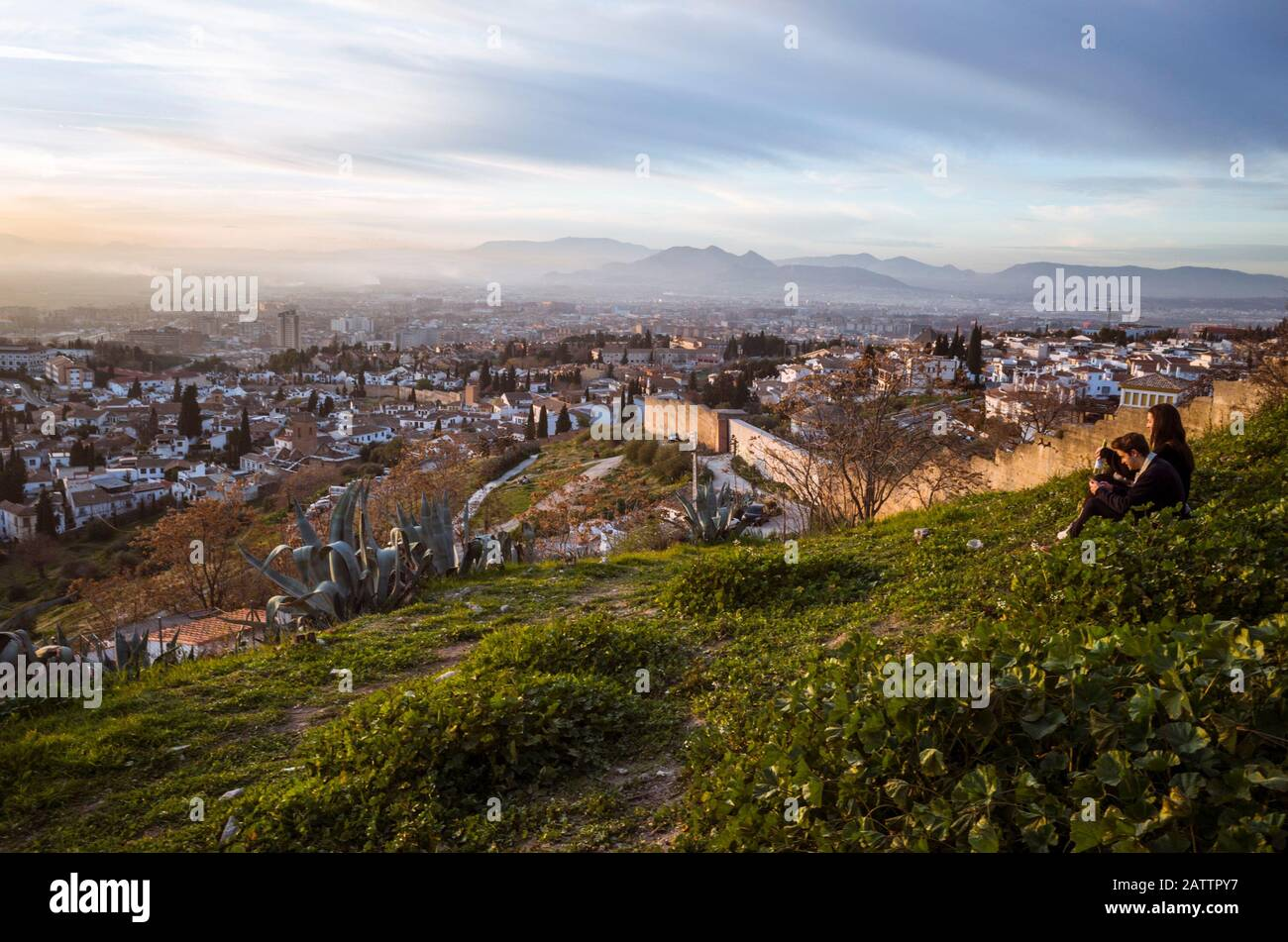Granada, Spanien - 17. Januar 2020: EIN Paar blickt auf Granada bei Sonnenuntergang an den Albaicin-Stadtmauern am San Miguel Alto Aussichtspunkt. Stockfoto