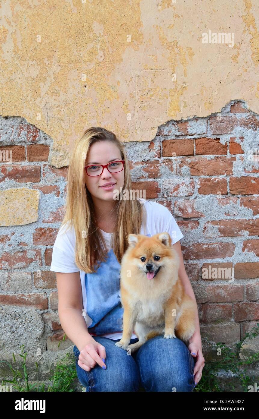 Junges, süßes Mädchen nebenan, das rote Brille, Jeans und T-Shirt trägt und mit ihrem Haustier vor der Grunge Ziegelwand posiert Stockfoto
