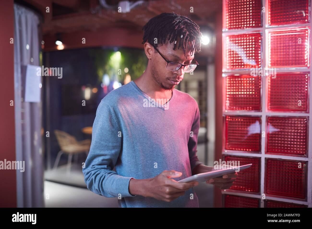 Taillen-Up-Porträt des zeitgenössischen afroamerikanischen Mannes mit digitalem Tablet während der Arbeit in futuristischen Büro-Innenräumen, Kopierraum Stockfoto