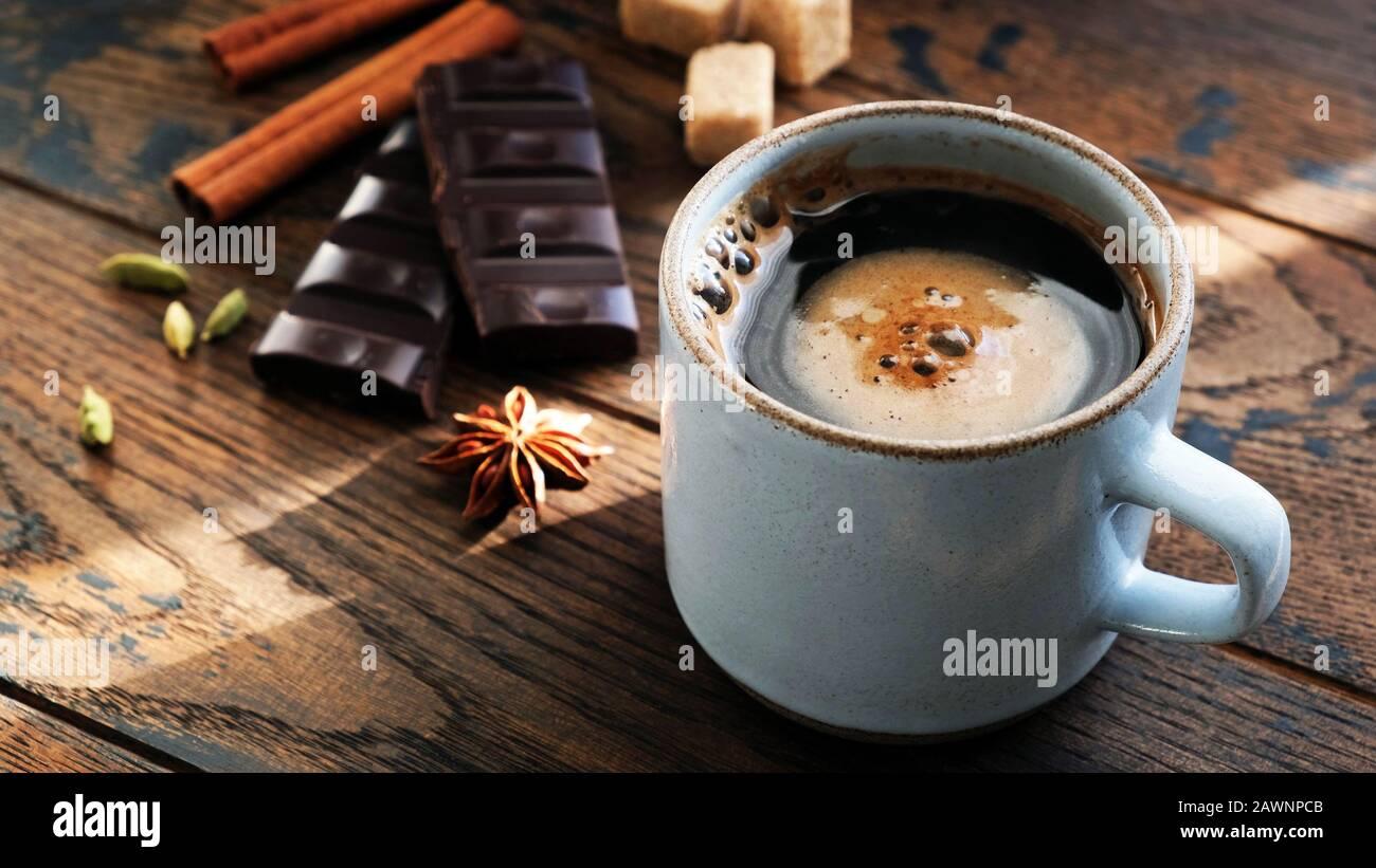 Kaffee und Gewürze Sternanis, Zimtstangen, Kardamompoden und dunkle Schokoladenrinde auf Holztisch. Frühstückskonzept Stockfoto
