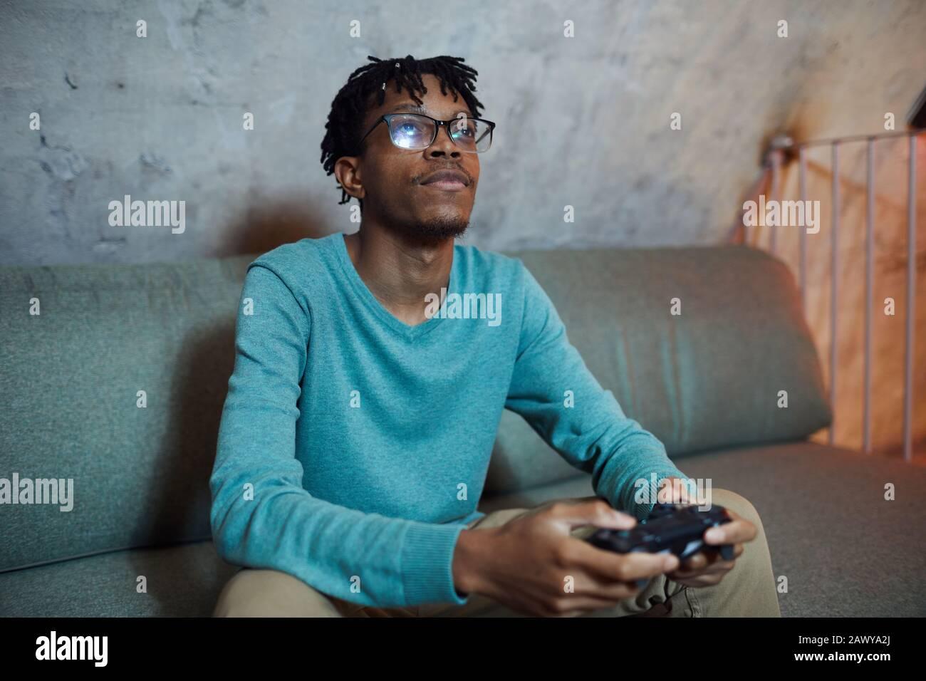 Portrait eines lächelnden afroamerikanischen Mannes, der Videospiele über Spielekonsole und Kopierraum spielt Stockfoto