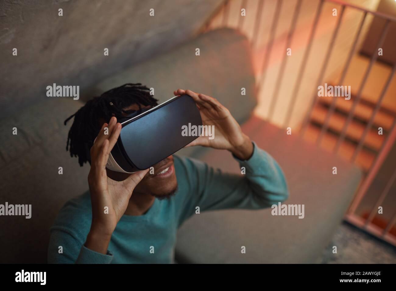 Hochwinkelansicht bei afroamerikanischem Mann, der VR-Ausrüstung trägt und gleichzeitig ein mitreißendes Erlebnis in futuristischem Interieur und Kopierraum genießt Stockfoto