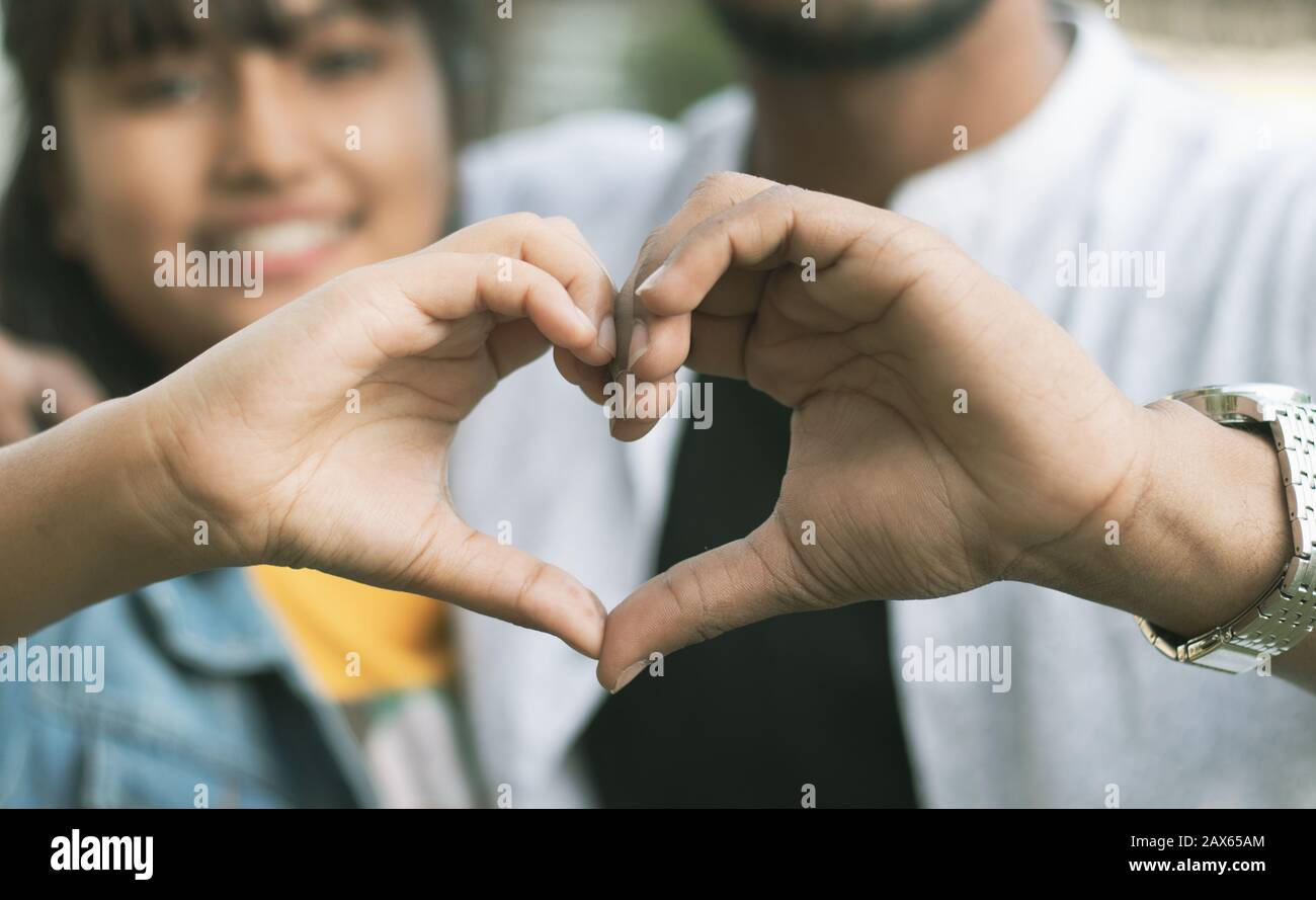 Ein Paar liebt es, Herz mit den Händen zu zeigen - Konzept der glücklichen Paarbeziehung und Zusammengehörigkeit Stockfoto