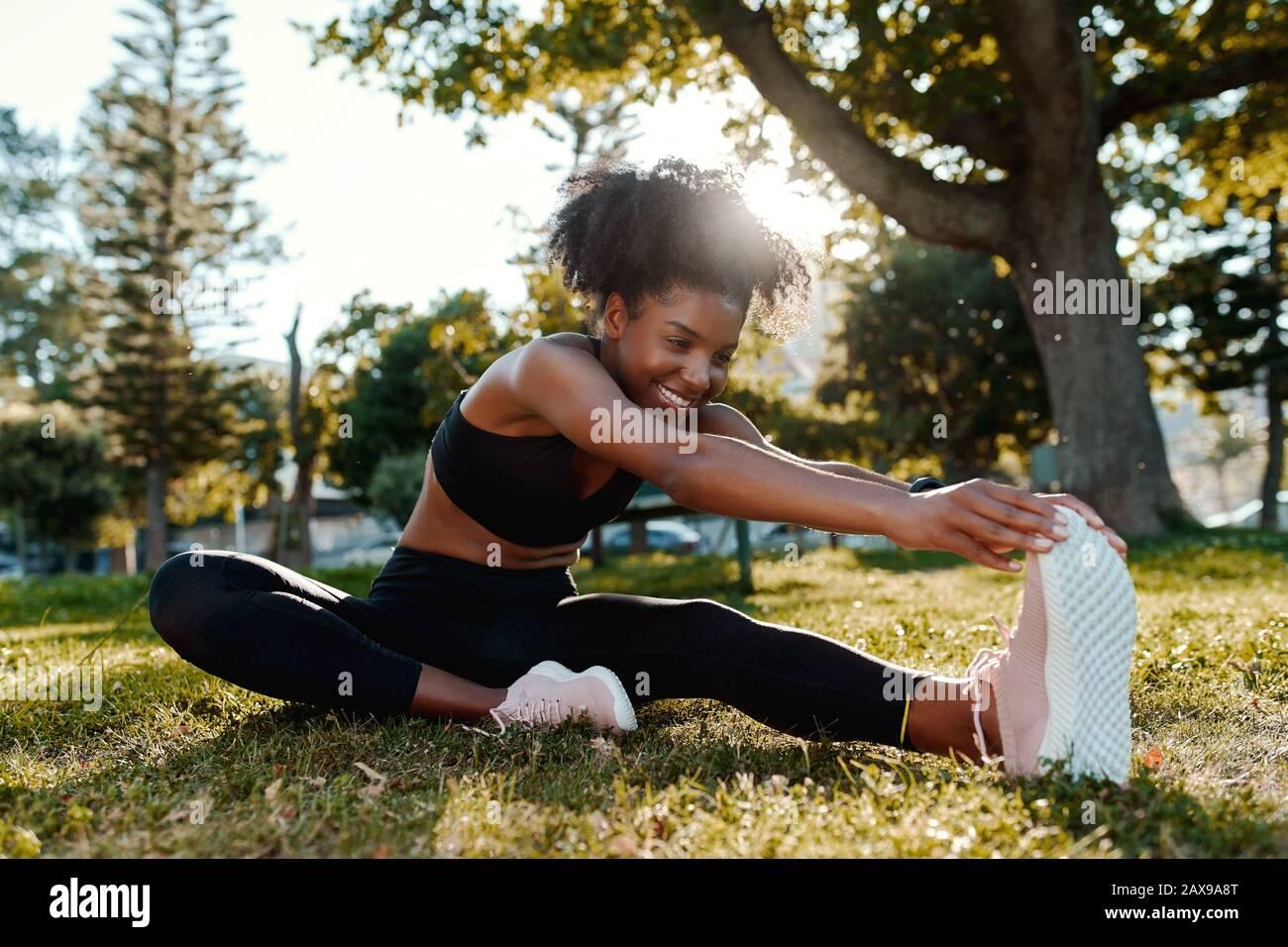 Lächelndes Porträt einer sportiv sitzenden afroamerikanischen jungen Frau auf dem Rasen, die ihre Beine im Park streckt - fröhliche junge schwarze Frau, die sich aufwärmt Stockfoto