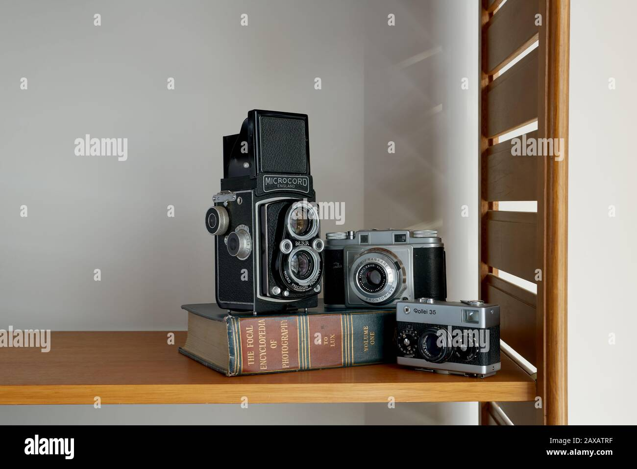 Ein Foto von drei Vintage-Kameras und ein Vintage-Fotobuch auf einem Regal. Stockfoto