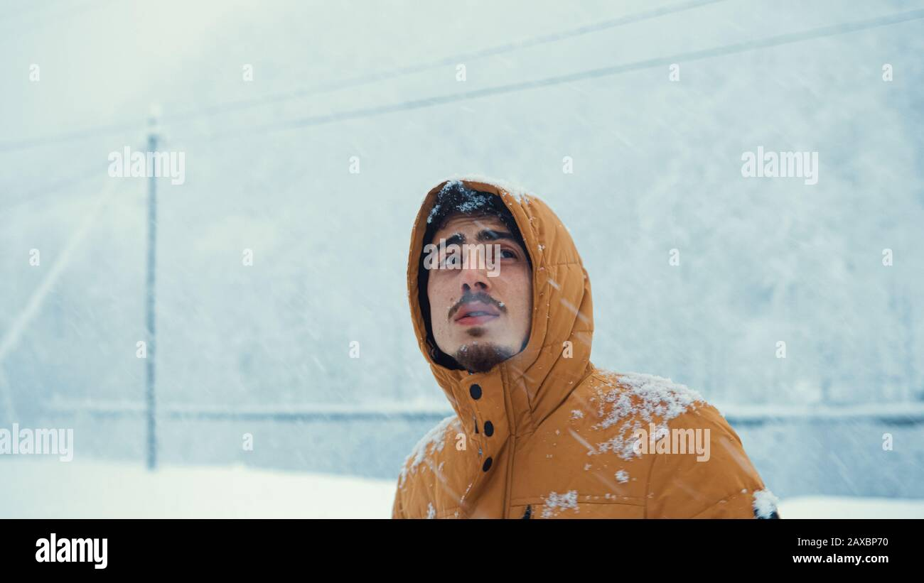 Porträt eines kalten Mannes, der einen Mantel trug, der im Schnee bei der Kälte Schnee gefangen hatte. Winterkonzept. Stockfoto