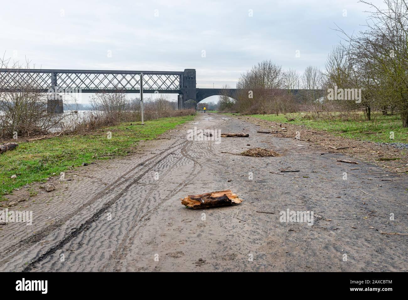 Ein Dirt-Bike-Weg am Ufer eines Flusses in Westdeutschland nach einem Hochwasser, sichtbarem Müll, Baumzweigen und Bahnbrücke. Stockfoto