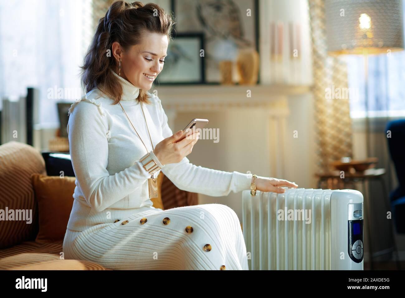 Fröhliche, moderne 40 Jahre alte Frau in weißem Pullover und Rock im modernen Wohnzimmer am sonnigen Wintertag auf dem Sofa in der Nähe weißer Elektroölradien sitzend Stockfoto