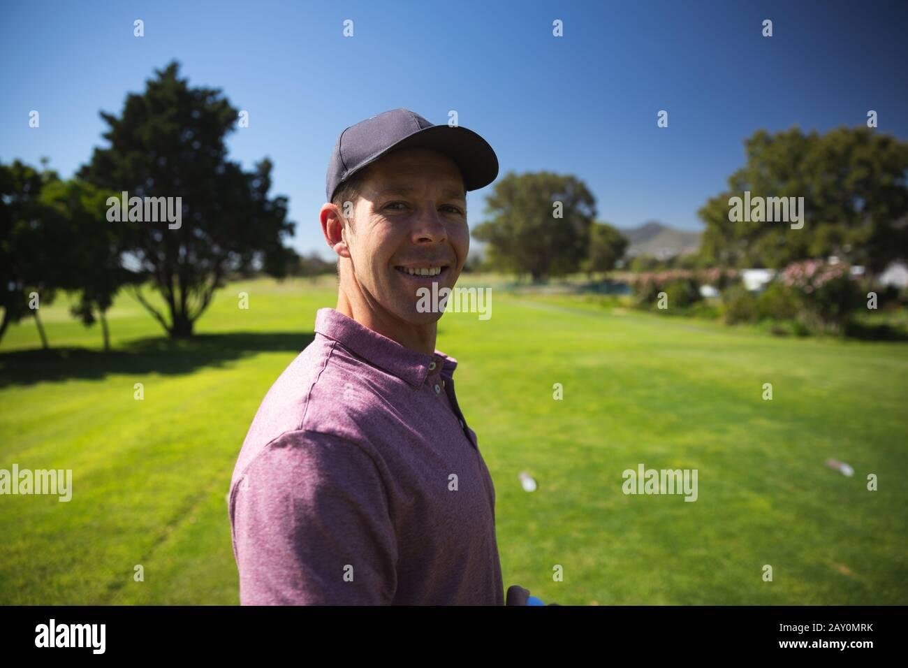 Golfer lächelnd und mit Blick auf die Kamera Stockfoto