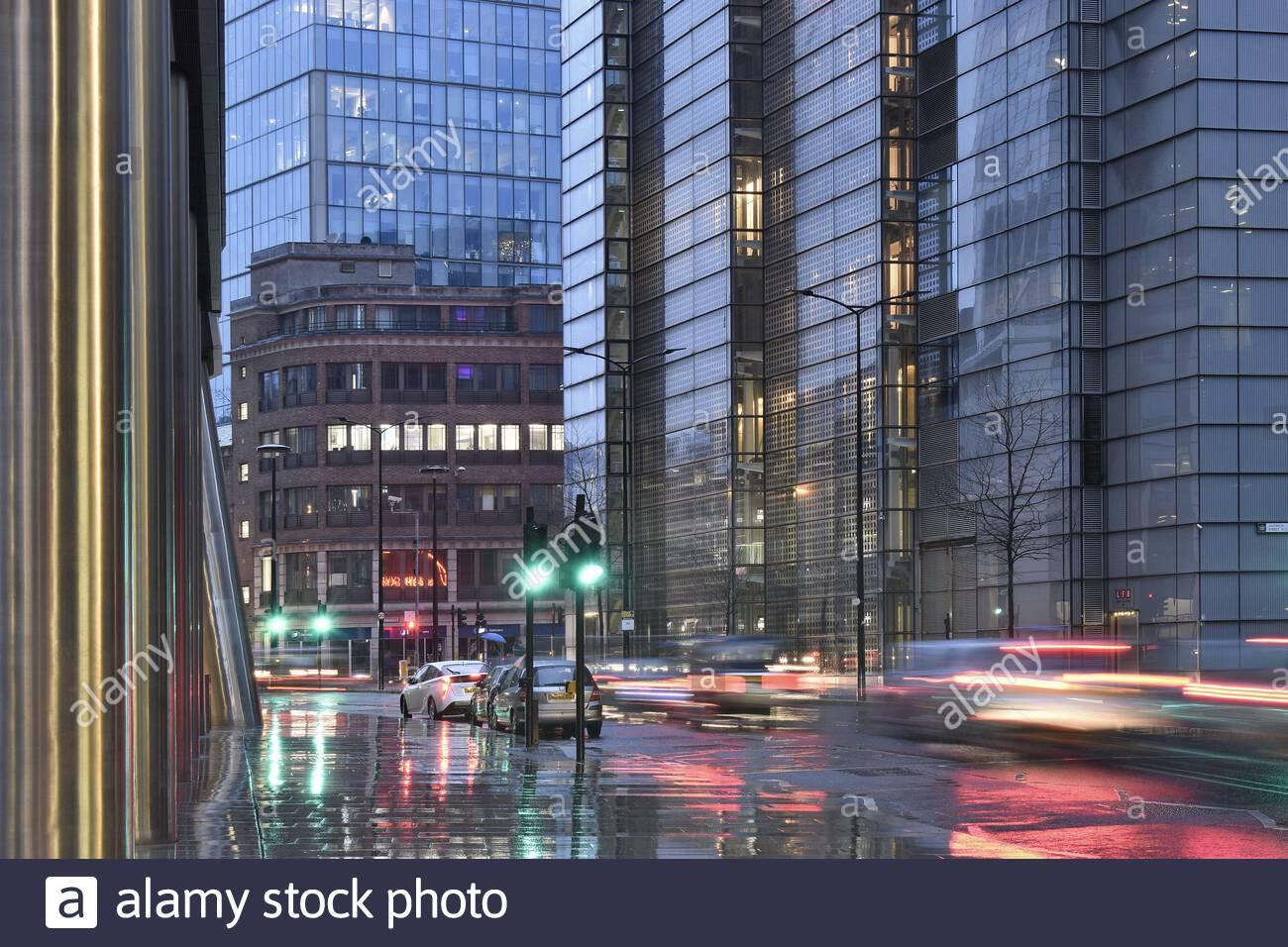 Die Straße mit den Autofahrern reflektiert über den regnerischen Tag und moderne Objekte in der City of London UK Stockfoto