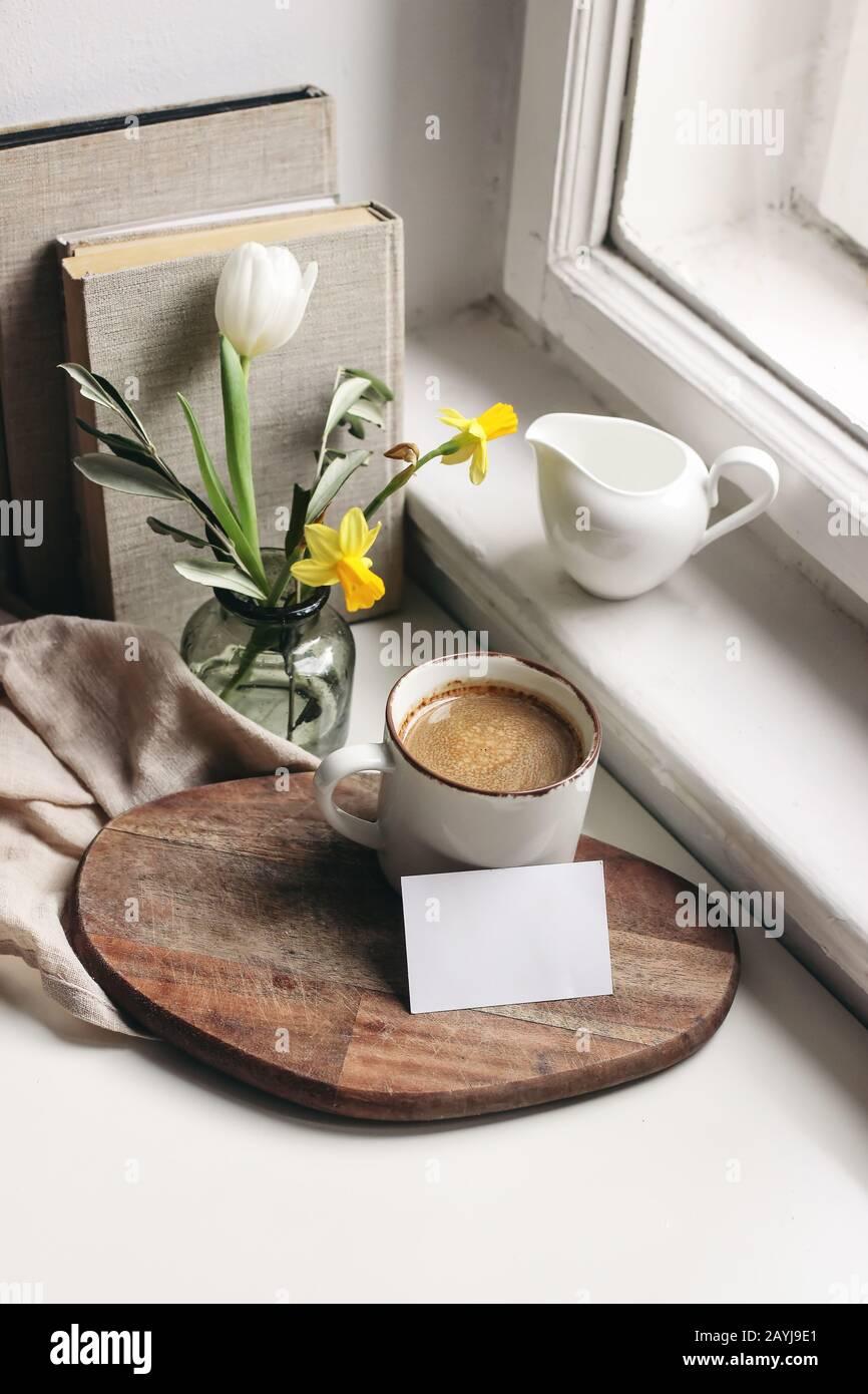 Gemütliches Stillleben im Osterfrühling. Visitenkarten-Mockup-Szene. Tasse Kaffee, Bücher, Holzschneidebrett, Milchkrug und Vase aus Narzissen und Tulpenfl Stockfoto