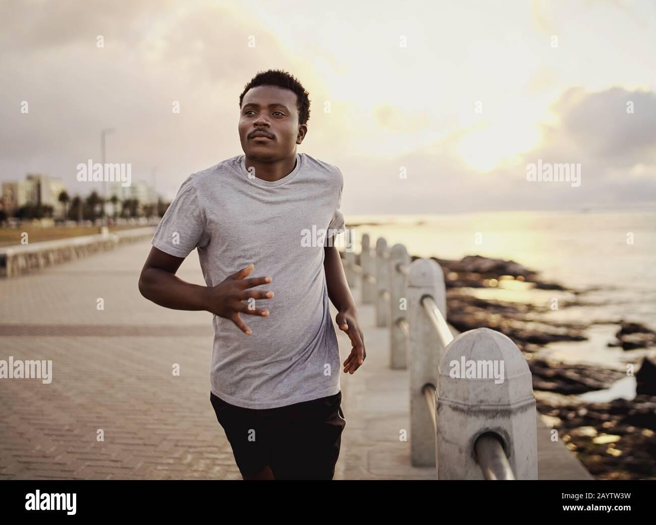 Ein selbstbewusster junger Athlet, der am frühen Morgen auf der Promenade am Meer läuft Stockfoto