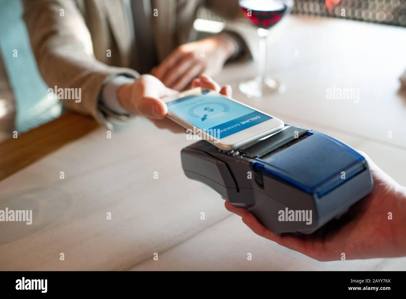 Horizontaler Nahaufnahme mit hohem Winkel von nicht erkennbarem Mann, der mit NFC auf dem Smartphone für das Essen im Restaurant bezahlt Stockfoto
