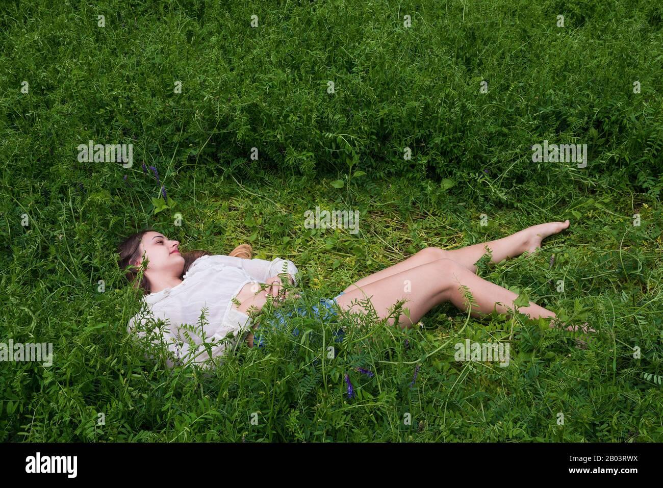 Eine junge Frau, die sich auf einem Gebiet der Fetch niederlegt. Stockfoto