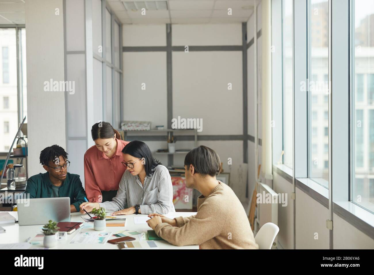 Junge Geschäftsleute sitzen am Tisch und planen gemeinsam während des Arbeitstages im Büro ein neues Projekt Stockfoto