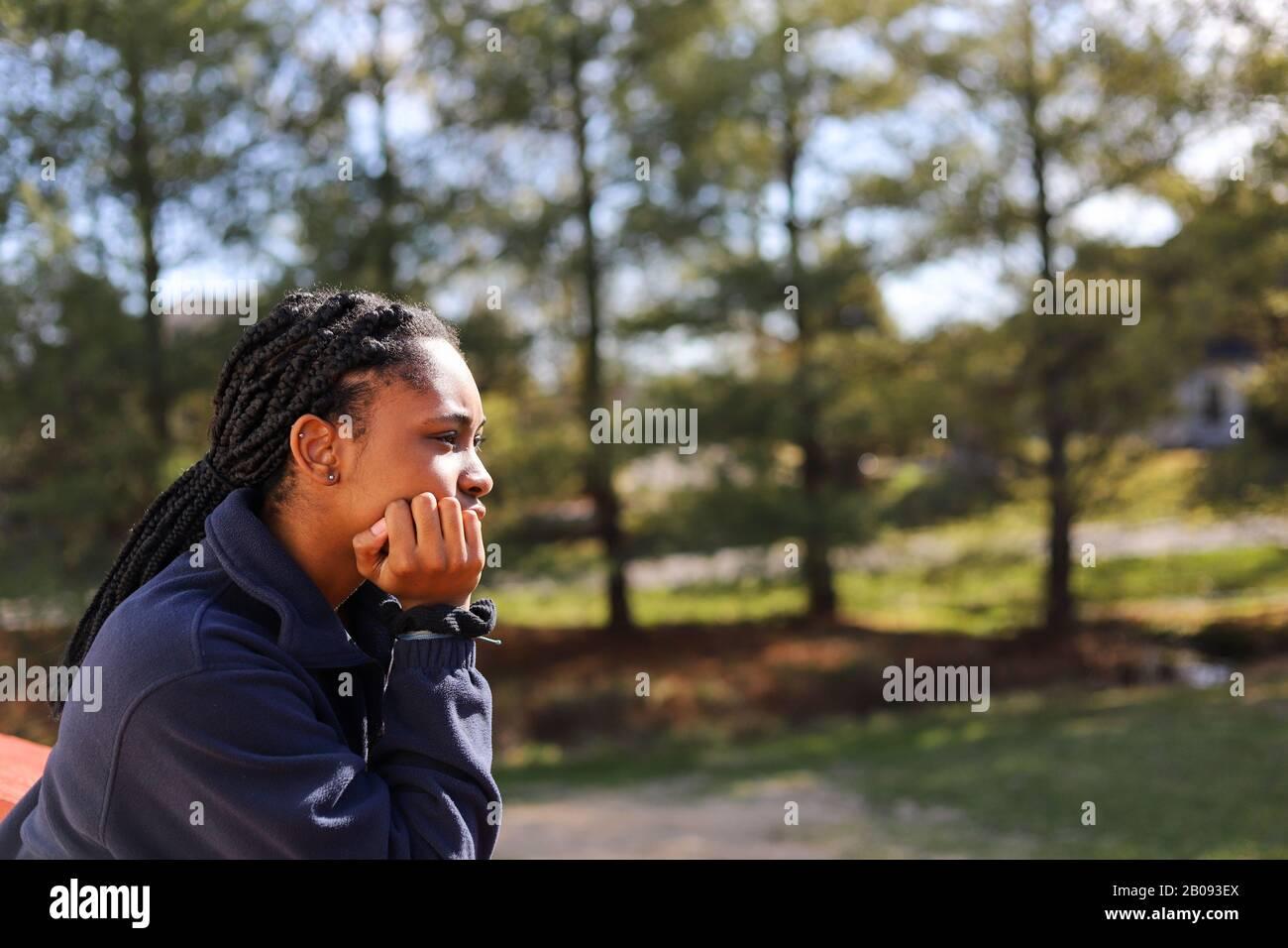 Porträt eines afroamerikanischen Teenagermädchens, das tief überlegt wegschaut Stockfoto