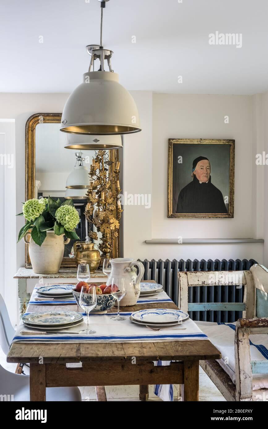 Das Porträt eines französischen Priesters aus dem 19. Jahrhundert ist ein ungezwungener Essbereich mit einem Tisch aus Eiche und einer ungarischen Sitzbank. Stockfoto