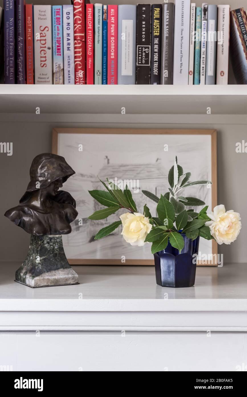 Frische Blumen und Bücher mit Statue und Kunstwerk Stockfoto