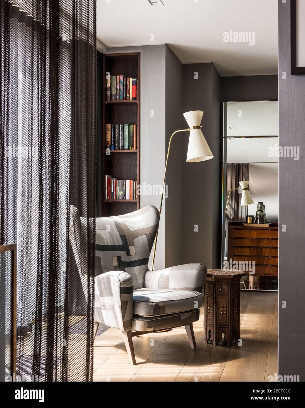 Diablo Modernist Bodenleuchte und gepolsterter Stuhl im Schlafzimmer der West London Wohnung Stockfoto