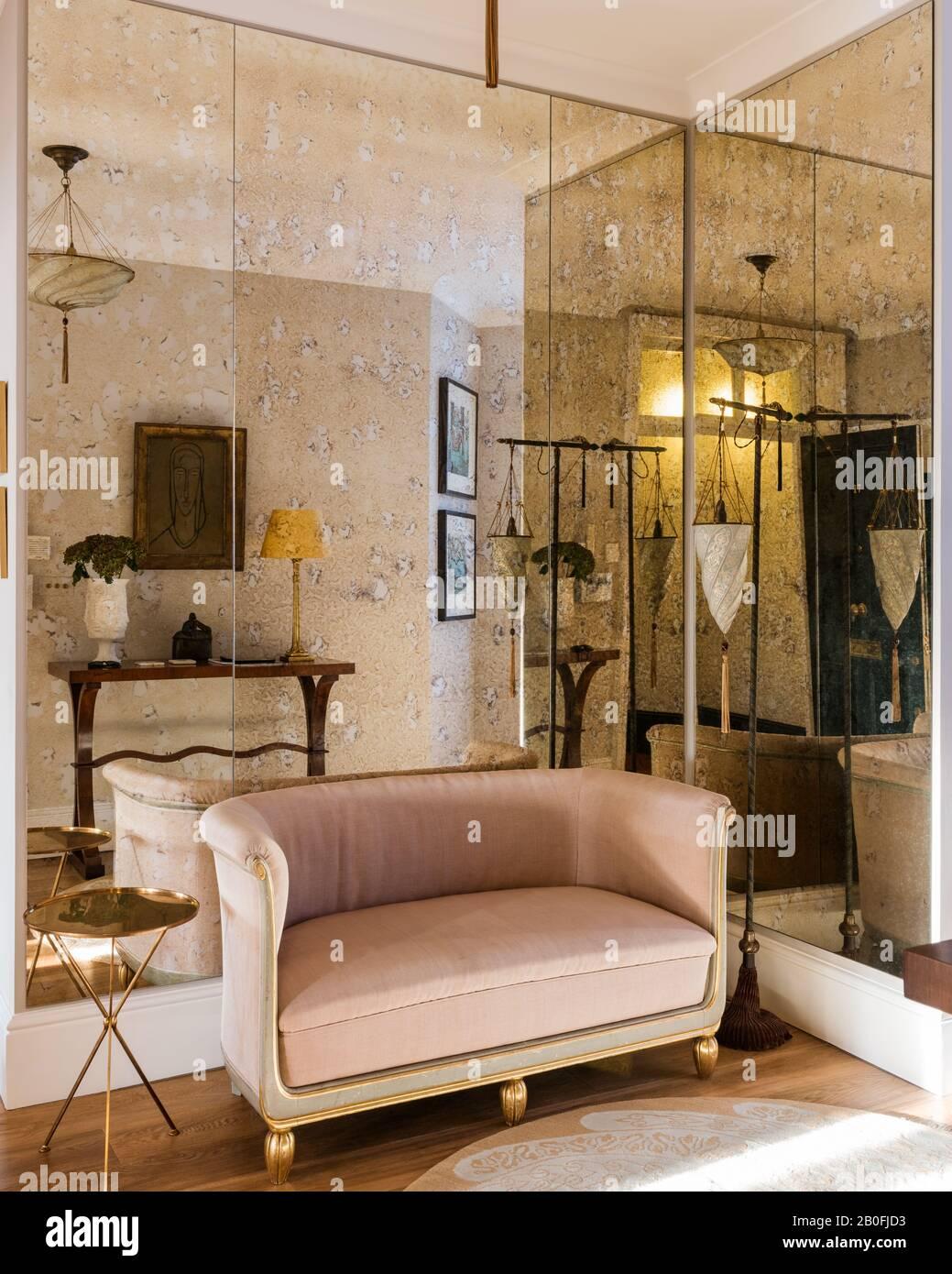 Gespiegelte Wand mit französischem Zweisitzer-Sofa, das in rosafarbenem samt bezogen ist. Stockfoto