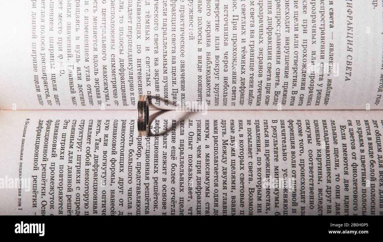 Ehering zwischen den Seiten eines Buches mit dem Sonnenlicht wirft einen herzförmigen Schatten Stockfoto