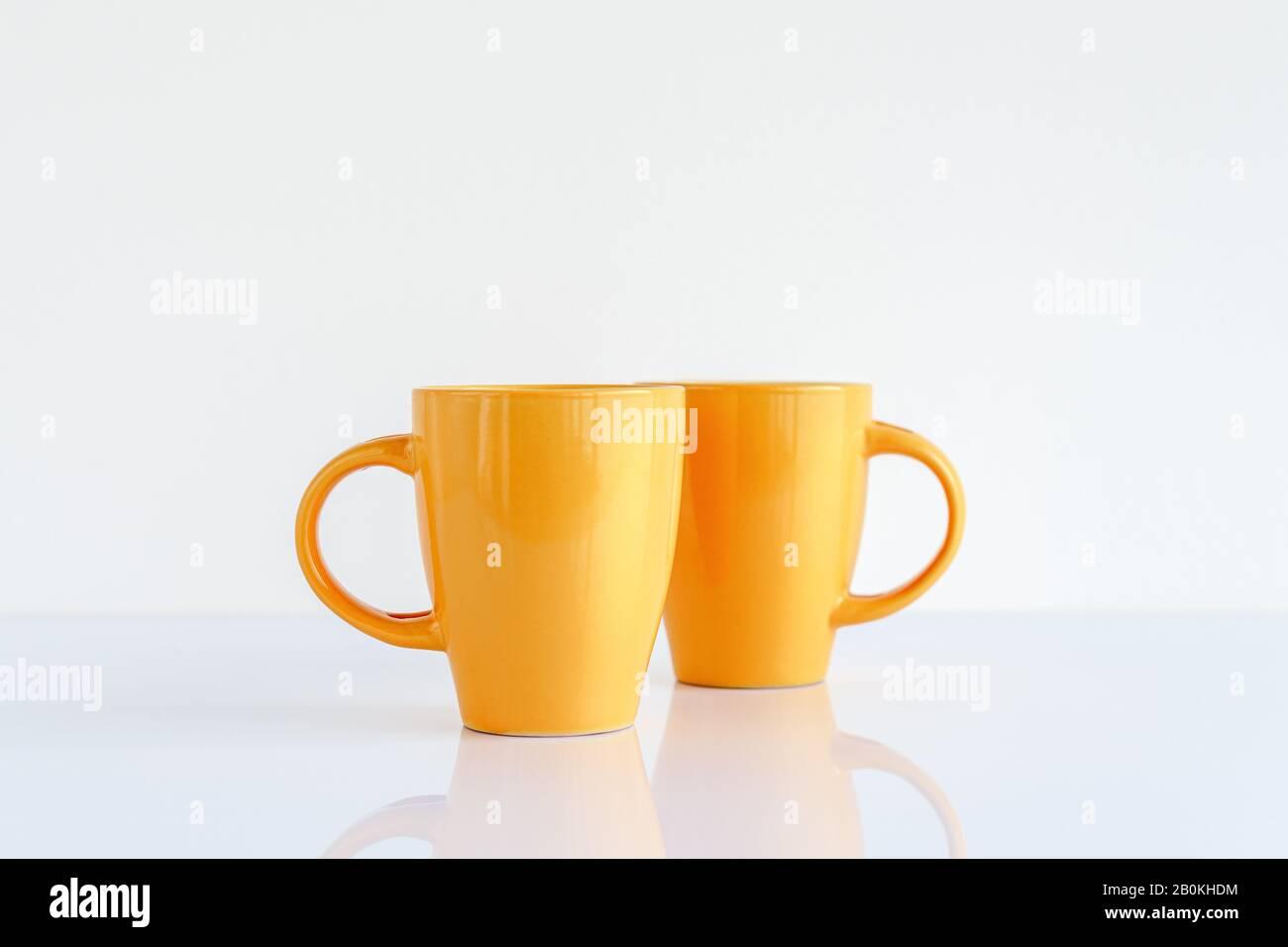 Zwei gelbe Kaffeetassen auf dem Tisch, Tassen aufspotten Stockfoto