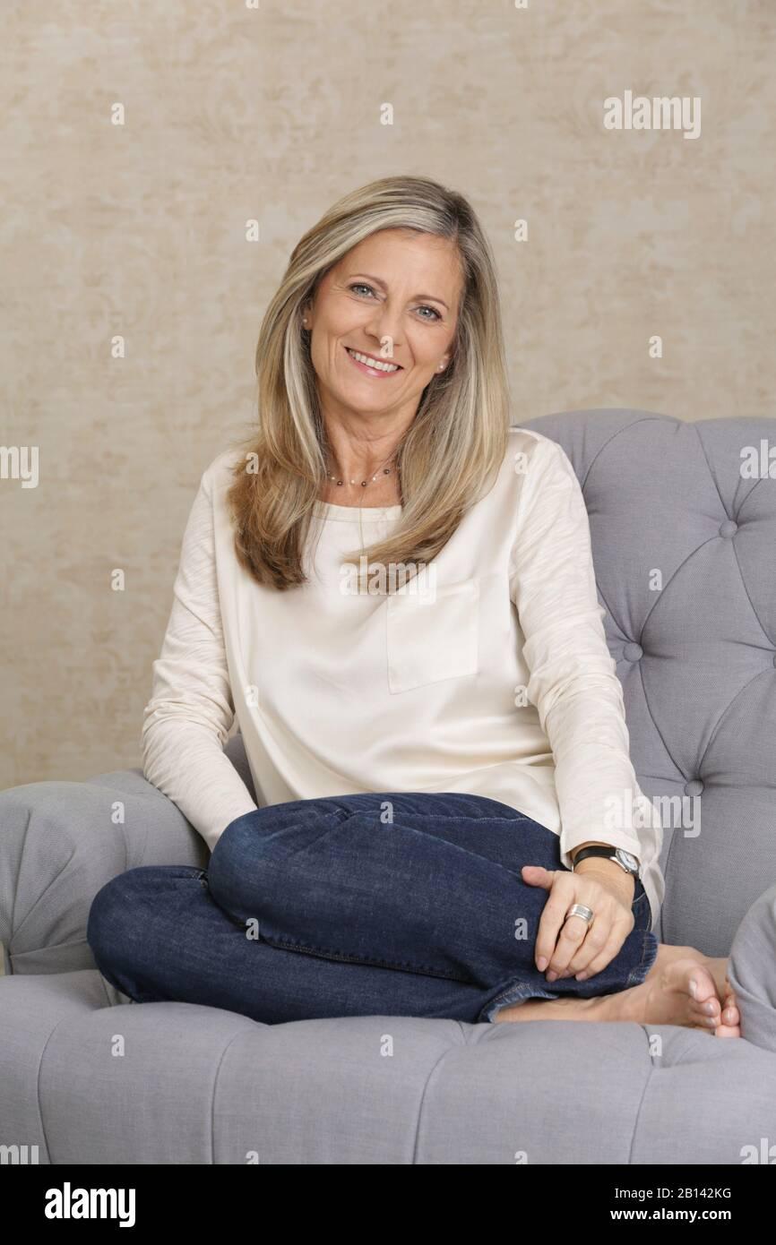 Frau mittleren Alters sitzen auf einer couch Stockfoto