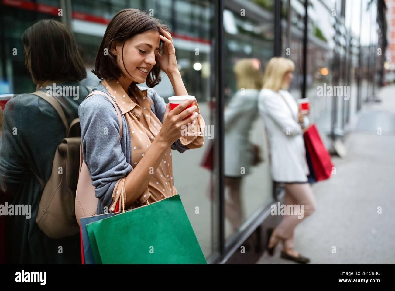 Fröhliche junge Frau, die nach dem Einkaufen in der Stadt Kaffee trinkt und mit Taschen spazieren geht. Stockfoto