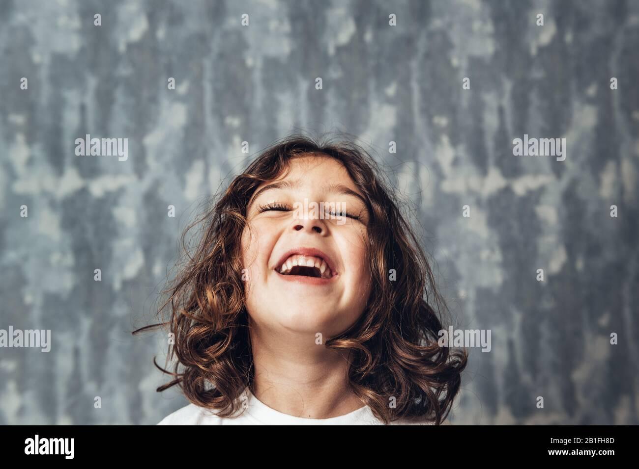 Porträt eines glücklichen kleinen Mädchens, das auf blauem Hintergrund lachen, glückliches Kindheits- und Lifestyle-Konzept, Platz für Text kopieren Stockfoto