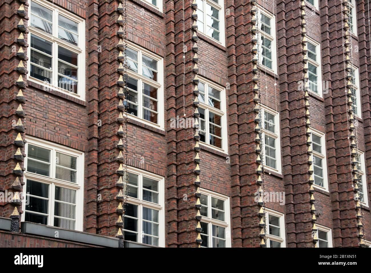 Braune Fassade aus Backstein des Palastgebäudes mit Fenstern und dekorativen senkrechten Kanten, von niedrigem Winkel im Vollformat betrachtet Stockfoto