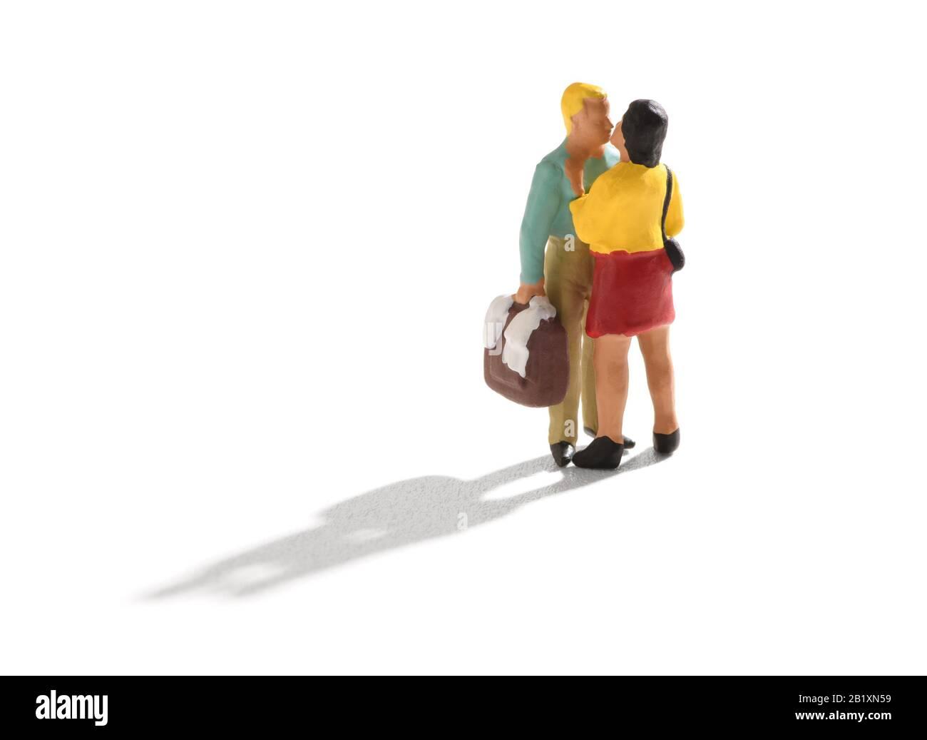 Kleines Miniaturpaar, Mann und Frau in legerer Kleidung, stehen und Küssen. Der Mann, der eine Tasche oder einen Koffer in der Hand hält. Isoliert auf weißem Rücken Stockfoto