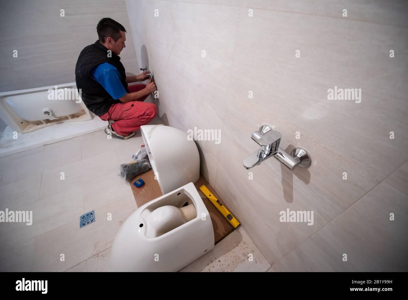 Professioneller Installateur, der in einem Bad arbeitet ...