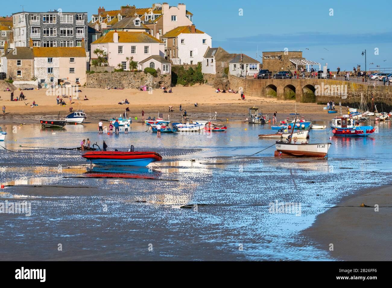 Blick über den Strand von St Ives Harbour zum Smeatons Pier mit Leuten am Strand, Booten im Hafen und Häusern, St Ives, Cornwall, Großbritannien Stockfoto