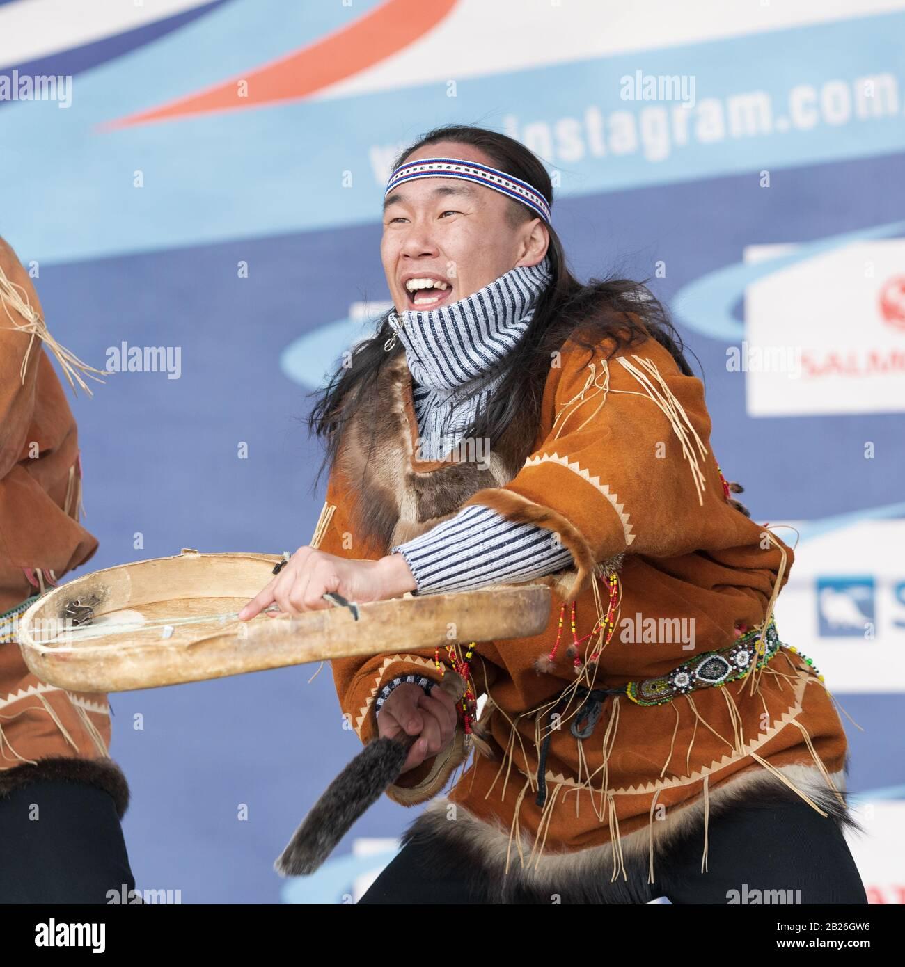 Aborigine-Tänzerin in nationalen Kleidungsstücken einheimischer Menschen emotionales Tanzen mit Tambourin. Konzert Koryak Dance Ensemble Mengo. Halbinsel Kamtschatka Stockfoto