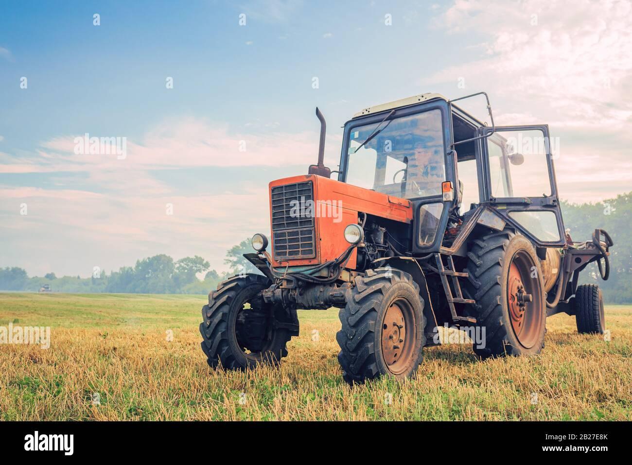 Alter Traktor düngt auf dem Feld an einem schönen blauen sonnigen Tag Stockfoto